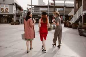 elegant women walking on street and drinking takeaway coffee