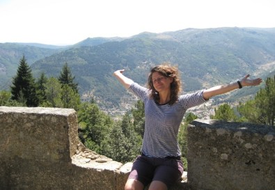 Laura with her arms out and the town of Manteigas in the background