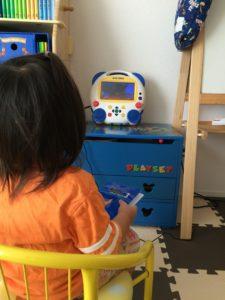 座ってDVDメイトでDVDを観る幼児の後ろ姿