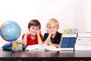 男の子2人が机で勉強しながらこちらを眺めてます