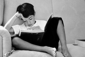 ソファに座って考え込みながら本を読む少年