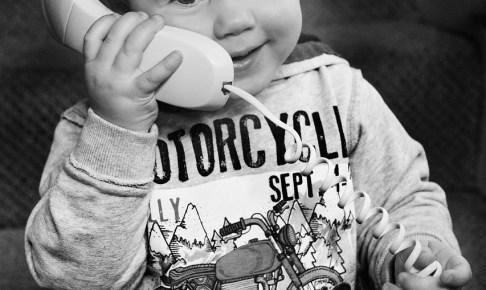 小さな男の子が固定電話の受話器で話してる