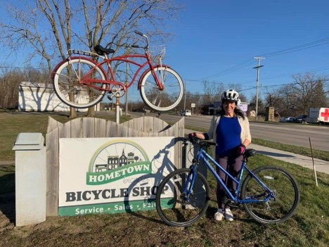 Hometown Bicycles Events Coordinator and Zumba instructor Leslie Barrett with her bicycle in front of the Hometown sign