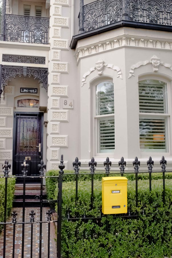 The yellow letterbox against the classic victorian facade creates a sense of what lays beyond