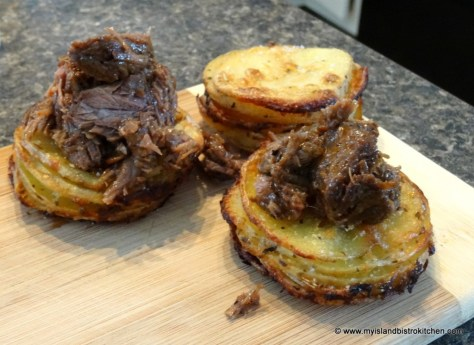 Braised beef atop a stack of potato slices