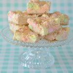 Glass pedestal dish filled with confetti-colored mini marshmallow squares set against a turquoise and white checked background
