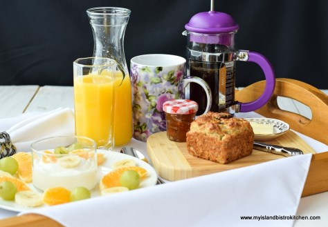 Gluten-free Banana Date Muffin on Breakfast Tray with a Carafe and Glass of Orange Juice, Plate of Fresh Orange, Grapes, and Yogurt, and French Press Coffee