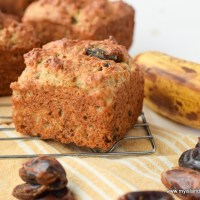 Large, perfectly domed Gluten-free Banana Date Muffins on a cooling rack surrounded by dates and a ripe banana