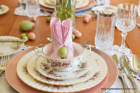 Close-up of placesetting featuring dinner plate, salad plate, and cream soup bowl. Dinnerware is white background with small pink and purple flower border. Pink napkin folded into the shape of bunny ears is placed inside the soup bowl