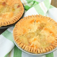 Two individual chicken pot pies in tin pie plates sitting on top of green and white plaid tea towel