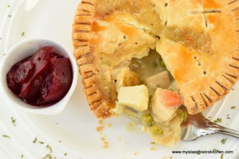 Individual chicken pot pie on white dinner plate with a small dish of cranberry sauce
