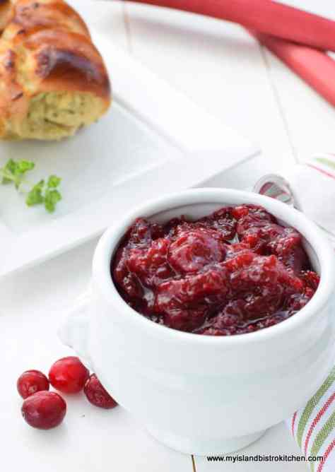 Small white bowl filled with Cranberry Rhubarb Sauce. Rolled stuffed turkey breast and stalks of rhubarb in background