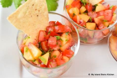 Small glass filled with fresh peach salsa