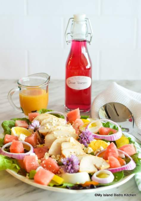 Plate of Salad with Bottle of Chive Vinegar and Small Jug of Vinaigrette in background