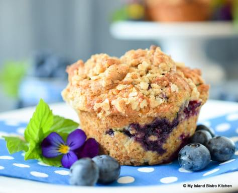 Close-up of a streusel-topped gluten-free Blueberry Zucchini Muffin on blue and white dotted napkin