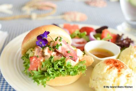 Lobster filling on a bed of green leafy lettuce sandwiched between a homemade hamburger roll
