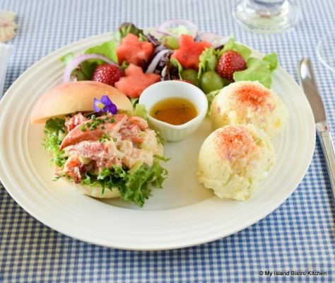 Plate of PEI Lobster Roll, Potato Salad, and Green Salad