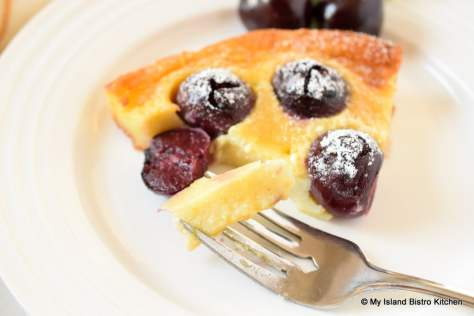 Bite of Cherry Clafoutis on fork tines