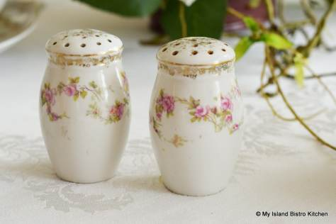 Antique salt and pepper set with tiny pink flowers on a white background