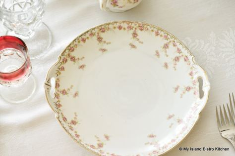 Top-down view of white serving plate with a border of tiny pink roses