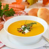 Bowl of Cream of Carrot Soup served with homemade rolls