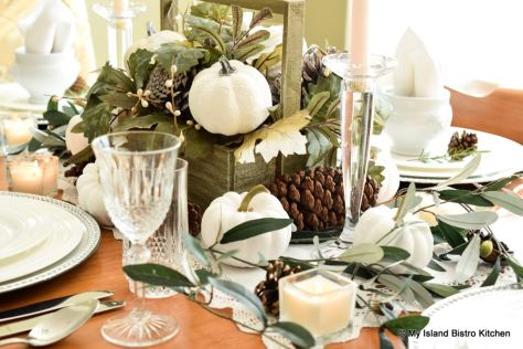 White pumpkins, shades of green, and brown pine cones are the theme for this fall tablesetting