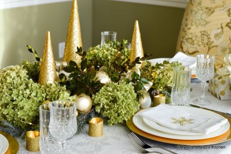 Gold trees, dried hydrangea, and holly leaves form a neutral holiday tablesetting