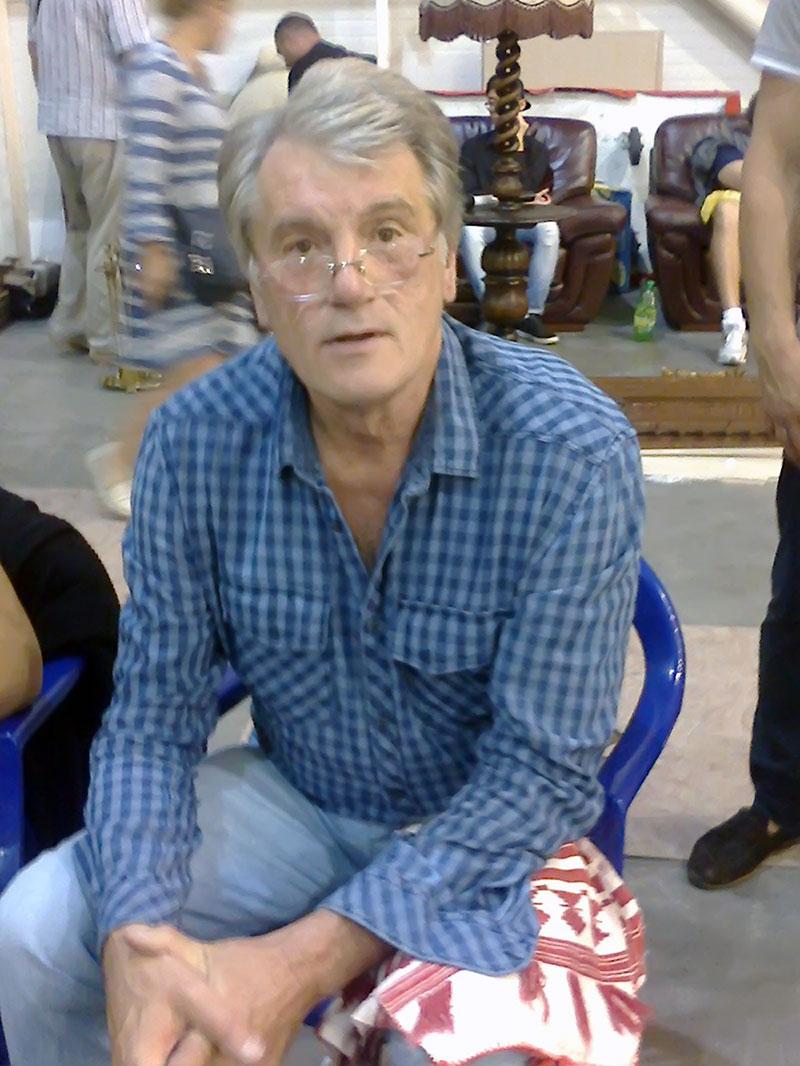 Виктор Андреевич Ющенко сидит себе на пластмассовом стуле и пьет кофе из бумажного стаканчика. А перед ним разложены старинные вышиванки. Торгует, значит.