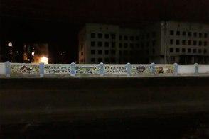 Вид на недостоеную больницу и забор разрисованный в национальных традициях изюмскими молодыми художниками