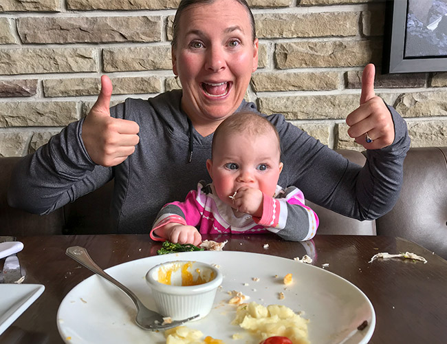 Happy Mom and happy baby because baby finished her meal at a restaurant