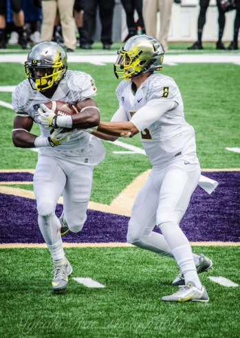 Oregon Quarterback Marcus Mariota (#8) passes off to Byron Marshall (#9). Mariota and Marshall made a great team with Mariota completing 24 of 31 passes and running on 13 plays and Marshall rushing 106 yards.