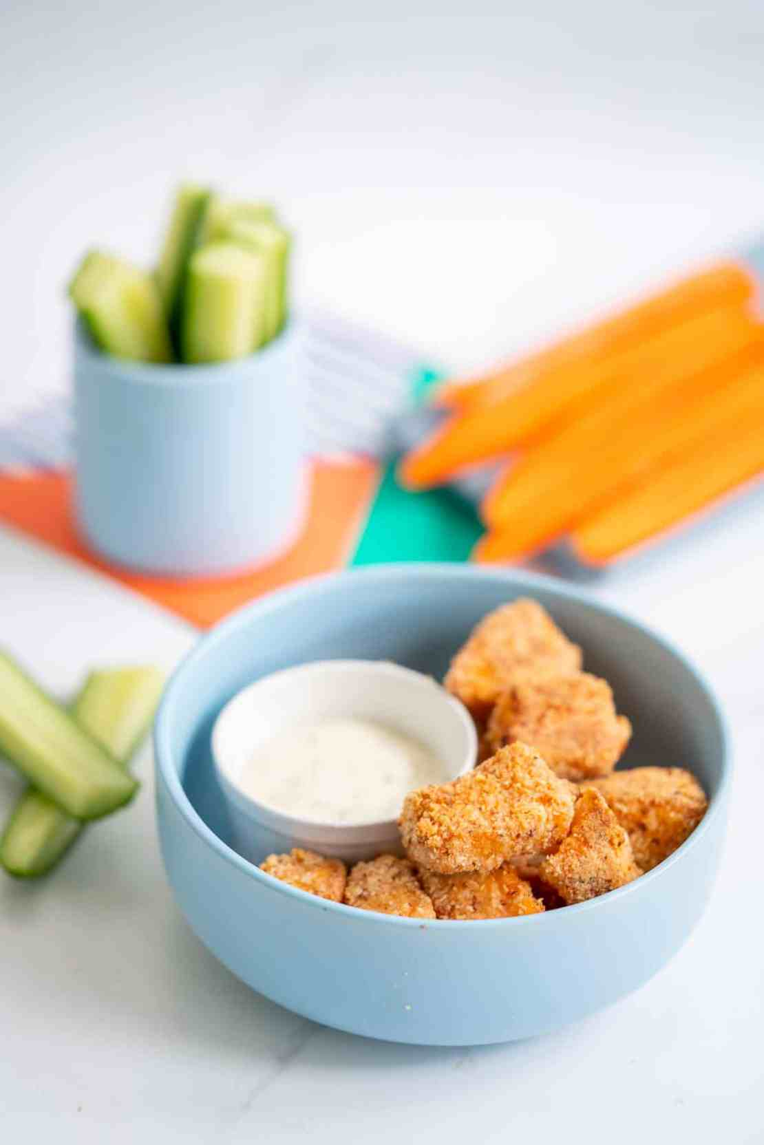 A blue bowl filled with salmon nuggets, cucumber and carrot sticks in the background.