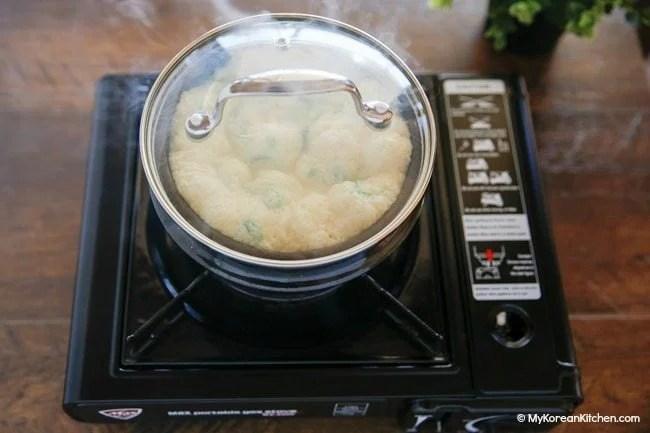 Cooking Korean steamed egg in a Korean hot stone bowl (ttukbaegi)