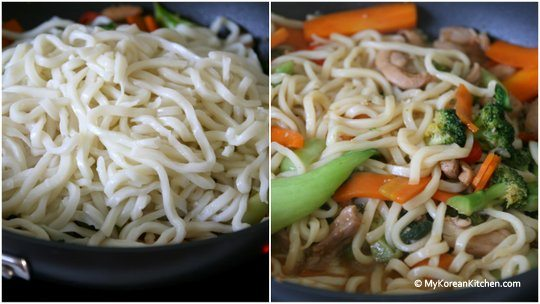 Mixing in udon noodles with chicken and veggies covered in Korean style sauce