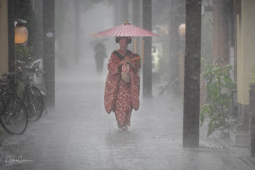 Maiko Kikusana walking under heavy rain, Kyoto