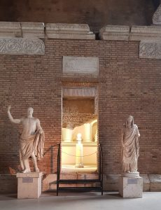Two Roman statues in front of a room that houses the urns of dead romans.
