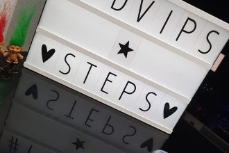 A white sign stating FDVIPs Steps with some trolls to the side of it and some glitter in tubs in front of it.