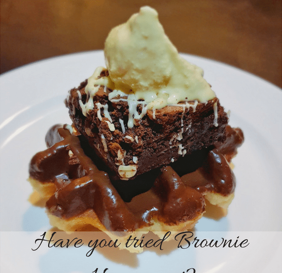 Have you tried Brownie Heaven Yet? Title picture with a Christmas pudding brownie placed on top of a waffle covered in Belgian chocolate with melted ice cream placed on top