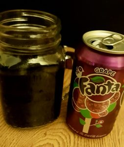 The grape Fanta drink, showing the can with its purple colouring and the drink in a cup next to it.
