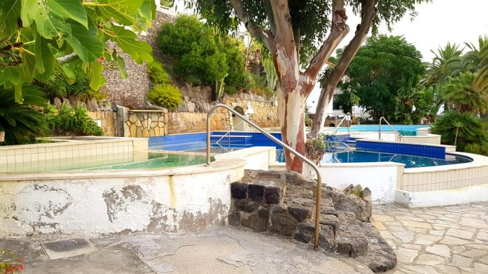 A landscape shot of the thermal pools. These can be seen with trees and foliage surrounding them.