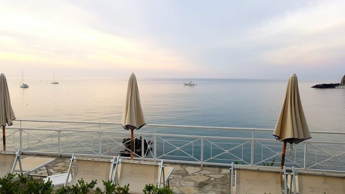 A picture of an early morning from the thermal pools at the Apollon club hotel. Along with a view of the sea, sun loungers and a white metal fence can be seen in the foreground.