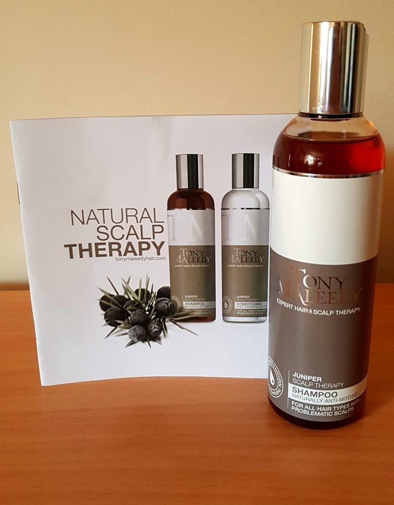A picture of the Tony Maleedy Scalp Therapy on a wodden desk with a magnolia background.