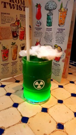 A photo of the luminescent nuclear daquiri available at Revolción de Cuba. This bright green drink is topped with a piece of white candy-floss and the drink is placed in front of an open drinks menu.