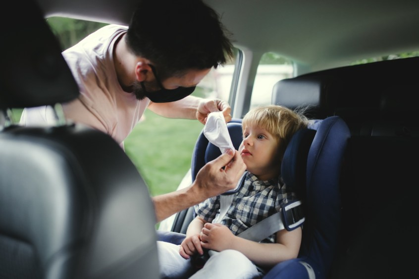 interstate custody - father putting mask on child in car seat