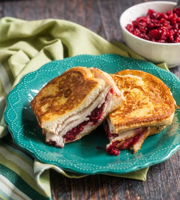 leftover turkey Cristo sandwich with a bowl of cranberry sauce in the background and a green tea towel
