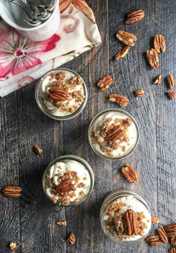 aerial view of 4 small jars with maple bacon low carb cheesecake and a few pecans scattered