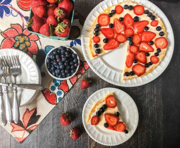 aerial view of fathead fruit pizza with strawberries and blueberries on white plates
