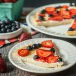 fathead fruit pizza with strawberries and blueberries on white plates