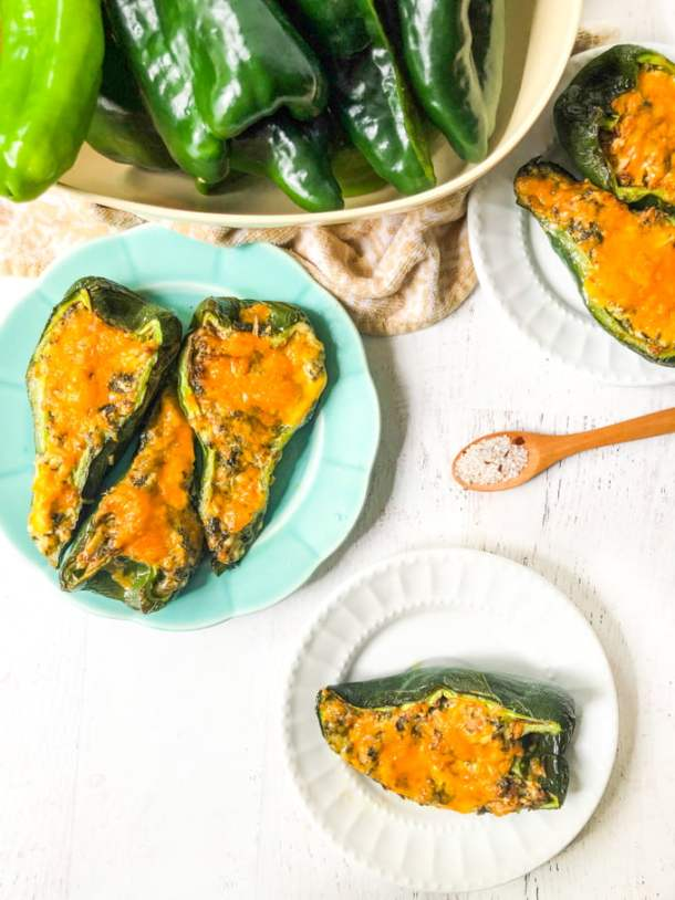 chicken stuffed poblano peppers on white and blue plates with bowl of raw peppers