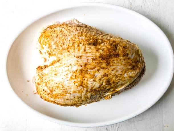 raw turkey breast with rub on it sitting on white platter